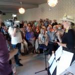 Rie med folk i salen og pressen