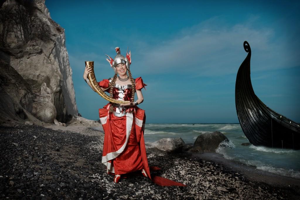 DANMARK. Anne Marie Helger er bestemt ikke bange for det farvestrålende og opulente. Her er hun gået i land på den danske kyst fra sit vikingeskib, og med sig har hun et af de navnkundige guldhorn. Det kan der sagtens komme teater ud af. Foto: Thomas Cato